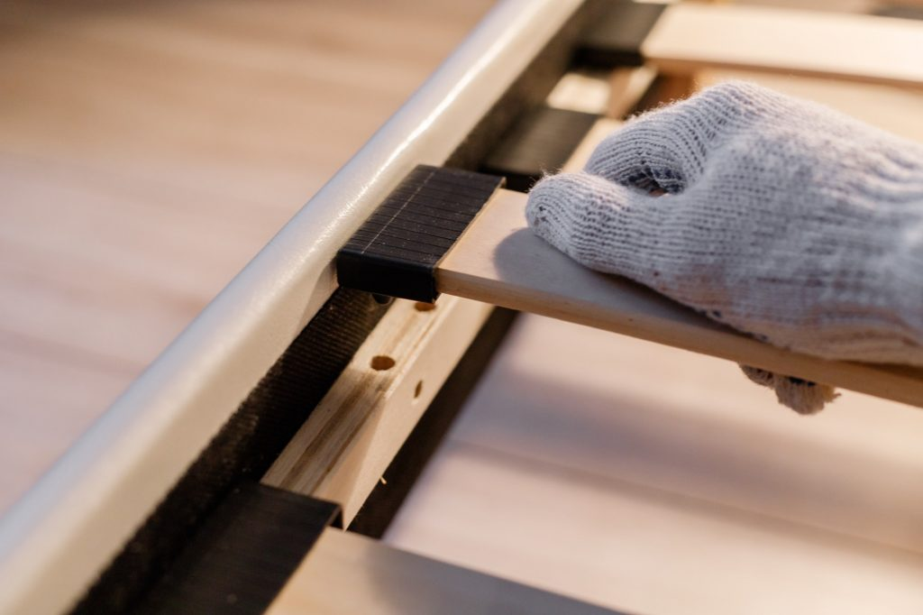 Frames Or Boxsprings? Male worker's hand in glove assembling bed, connecting slats to bed frame.