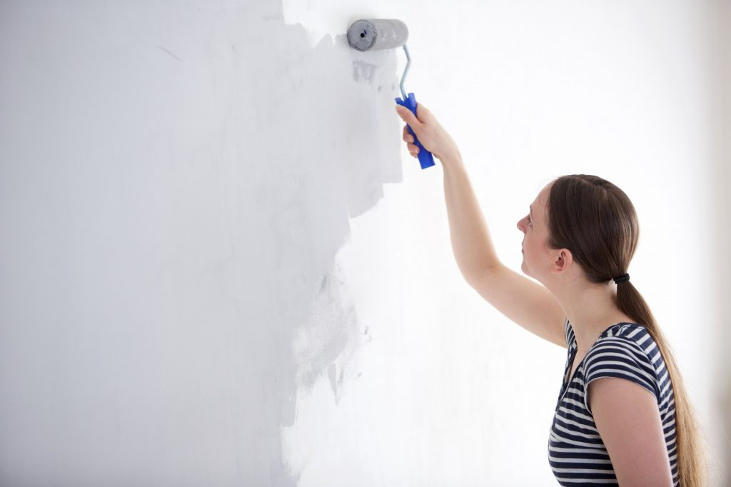 Young woman painting wall of her home.